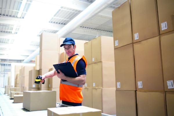 Arbeiter im Versandhandel scannt Pakete am Fliessband zur Lieferung ein
